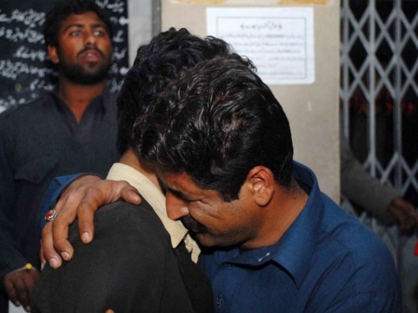 Relatives of the victims comfort each other at PIMS Hospital in Islamabad. PHOTO: ONLINE